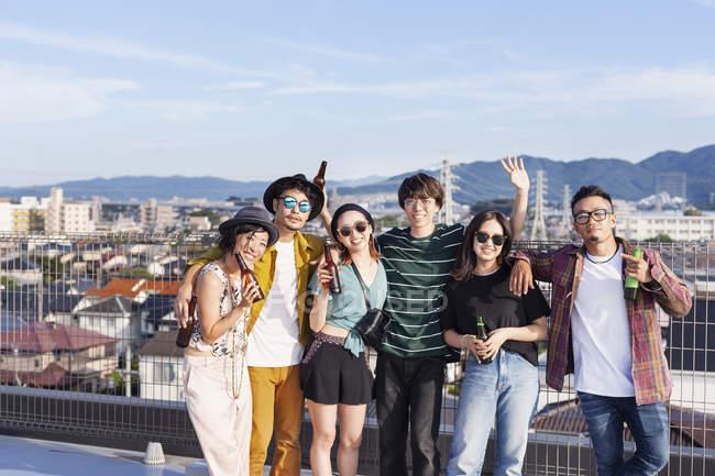 Группа молодых японских мужчин и женщин, стоящих на крыше в городской обстановке. — стоковое фото