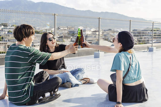 Young Japanese man and women sitting on rooftop in urban setting, toasting with beer bottles. — Stock Photo
