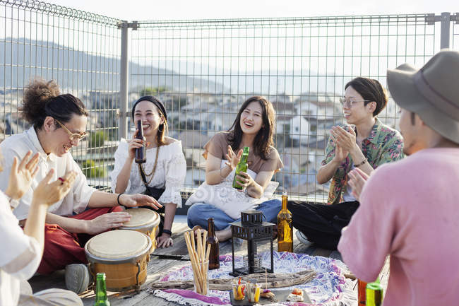 Group of young Japanese men and women sitting on rooftop in urban setting, drinking beer and playing drums. — Stock Photo