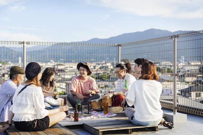 Groupe de jeunes Japonais et Japonaises assis sur le toit en milieu urbain, buvant de la bière et jouant de la batterie . — Photo de stock
