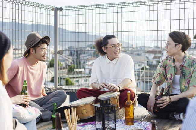 Группа молодых японских мужчин и женщин, сидящих на крыше в городской обстановке, пьющих пиво и играющих на барабанах. — стоковое фото