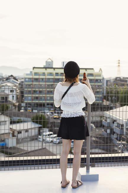 Vue arrière de la jeune femme debout sur le toit en milieu urbain . — Photo de stock