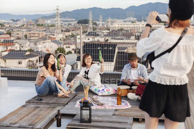Gruppo sorridente di giovani giapponesi e donne sul tetto in ambiente urbano, bere birra e fingersi donna scattare foto . — Foto stock