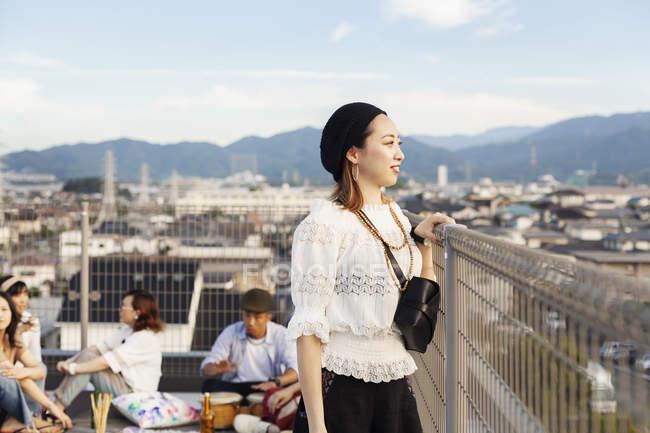 Sourire jeune femme japonaise debout sur le toit en milieu urbain avec des amis en arrière-plan . — Photo de stock