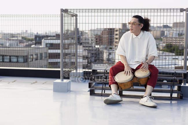 Японец, сидящий на крыше в городской обстановке, играющий на барабанах. — стоковое фото