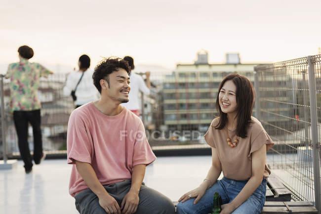 Souriant jeune Japonais homme et femme assis sur le toit en milieu urbain . — Photo de stock