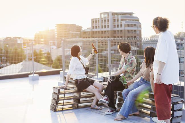 Groupe de jeunes hommes et femmes assis sur le toit en milieu urbain . — Photo de stock