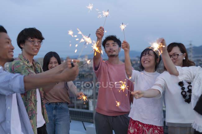 Группа молодых японских мужчин и женщин с искрами на крыше в городских условиях. — стоковое фото