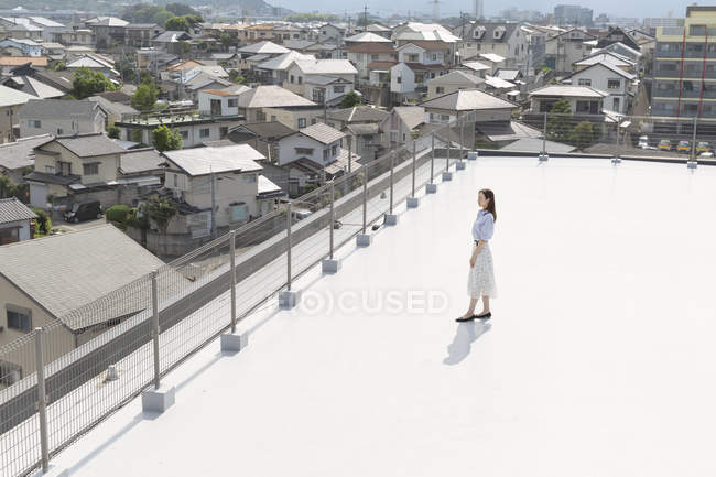 High angle view of young Japanese woman standing on rooftop in urban setting. — Stock Photo