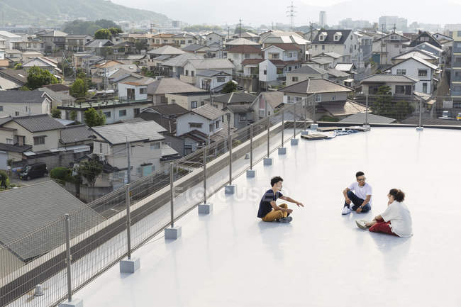 High angle view of young Japanese men sitting on rooftop in urban setting. — Foto stock