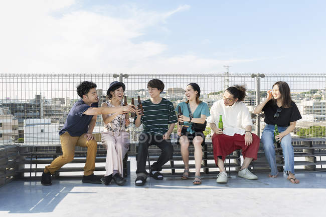 Smiling group of young Japanese men and women sitting with beer bottles on rooftop in urban setting. — Stock Photo