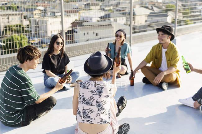 Groupe souriant de jeunes Japonais et Japonaises assis sur le toit en milieu urbain . — Photo de stock