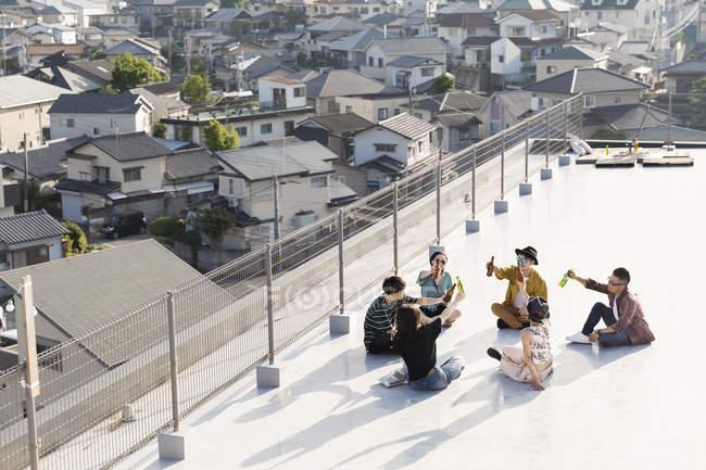 Vue en grand angle du groupe de jeunes hommes et femmes japonais assis sur le toit en milieu urbain . — Photo de stock