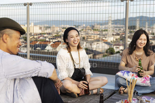 Smiling group of young Japanese man and women sitting on rooftop in urban setting. — Stock Photo