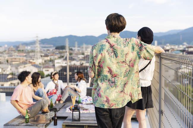 Группа молодых японских мужчин и женщин на крыше в городской среде. — стоковое фото
