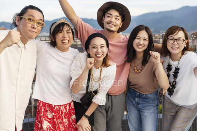 Lächelnde Gruppe junger japanischer Männer und Frauen, die auf einem Dach in urbaner Umgebung stehen. — Stockfoto