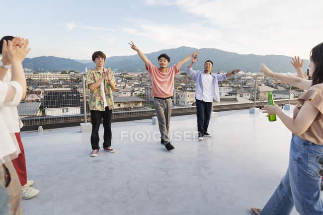 Jeunes hommes japonais dansant sur le toit en milieu urbain . — Photo de stock