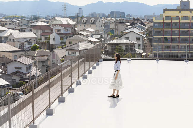 High angle view of Japanese woman standing on rooftop in urban setting. — Stock Photo