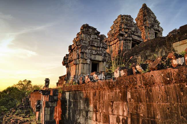 Angkor Wat, temple khmer historique du XIIe siècle et site du patrimoine mondial de l'UNESCO. Arches et blocs de pierre sculptés et marches au coucher du soleil. — Photo de stock