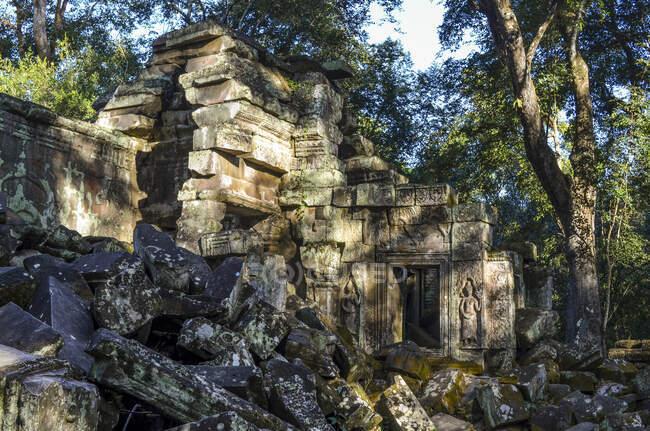 Angkor Wat, temple khmer historique du XIIe siècle et site du patrimoine mondial de l'UNESCO. Arches et blocs de pierre sculptés dans les ruines des pavillons des temples, avec des arbres dominant les bâtiments. — Photo de stock