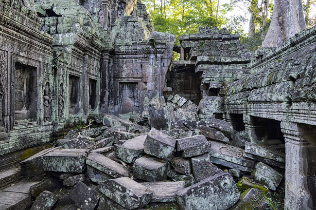 Angkor Wat, a 12th century historic Khmer temple and UNESCO world heritage site. Arches and carved stone blocks, fallen masonry and structures being overgrown by the jungle. — Stock Photo