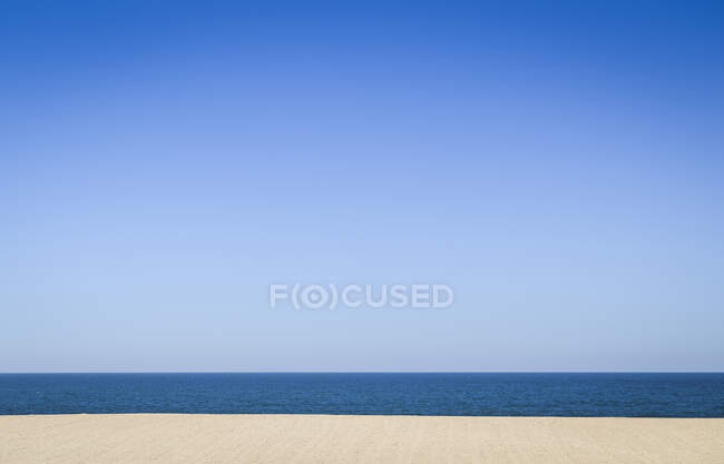Empty sandy beach and ocean, view out to sea under a clear blue sky. — Stock Photo