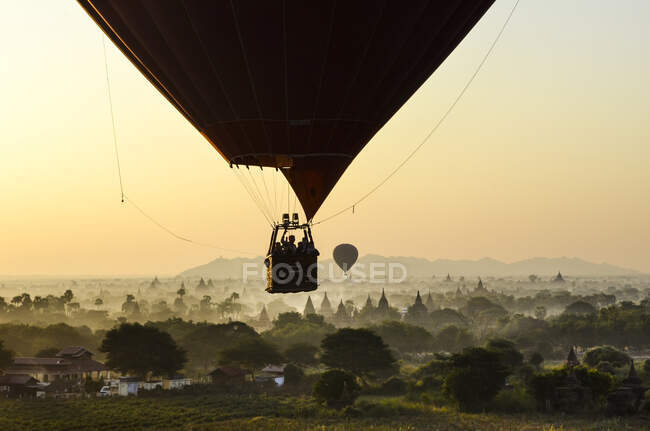Avión de aire caliente sobre el paisaje con templos al atardecer, Bagan, Myanmar.. - foto de stock