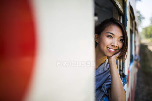 Smiling young woman riding on a train, looking out of window. — Stock Photo