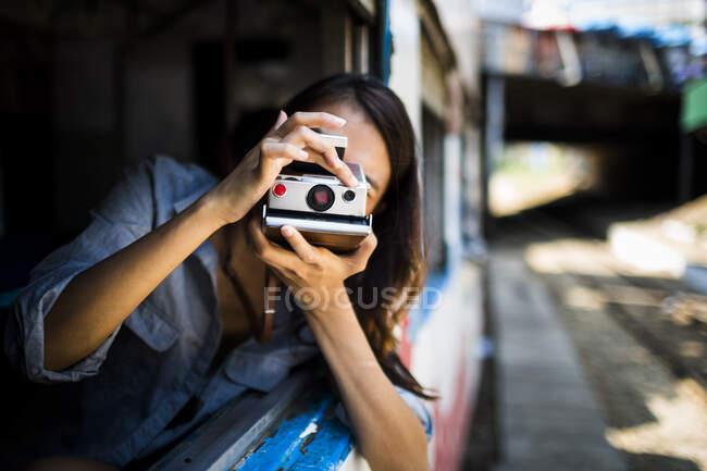 Mujer joven que conduce en un tren, mirando fuera de la ventana, tomando fotos. - foto de stock