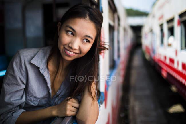 Посмішка молода жінка їде поїздом, дивлячись у вікно. — стокове фото