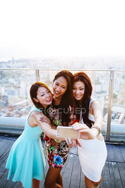 Trois femmes se tenant debout sur le toit d'un immeuble à Singapour et se faisant passer pour elles avec un téléphone cellulaire. — Photo de stock