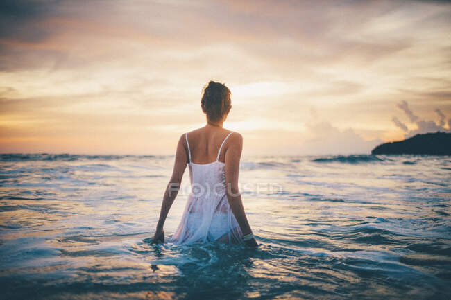 Rear view of young woman wearing a white dress walking in the ocean at sunset. — Stock Photo