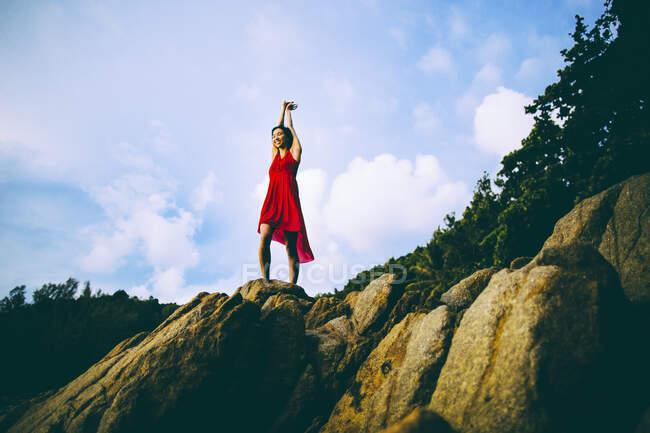 Vista de bajo ángulo de mujeres jóvenes vestidas de rojas de pie sobre rocas. - foto de stock