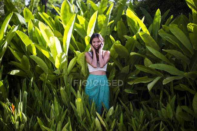 Jeune femme debout dans une forêt ombrophile au feuillage vert luxuriant. — Photo de stock