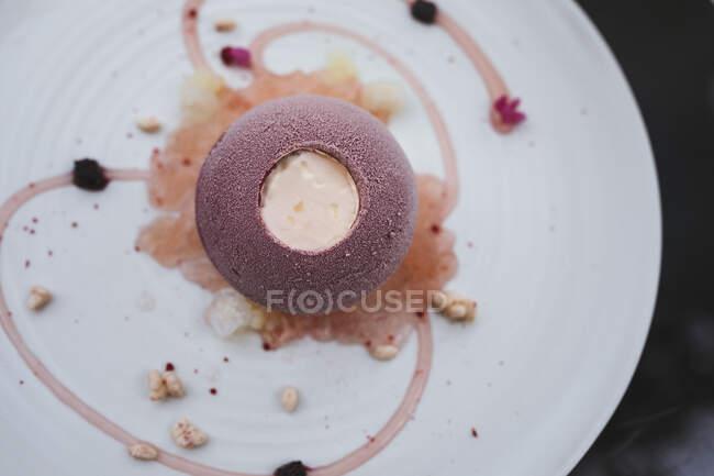 Високий кут, близький до плити десерту з кассіс-бомбе і цвітної квітки йогурт, хойя граніта і юдзу перли. — стокове фото