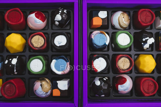 High angle close up of selection of bonbons in a purple and black box. — Stock Photo