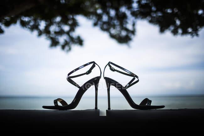 Primo piano di paio di sandali a stiletto lucidi, fogliame d'albero e oceano sullo sfondo . — Foto stock
