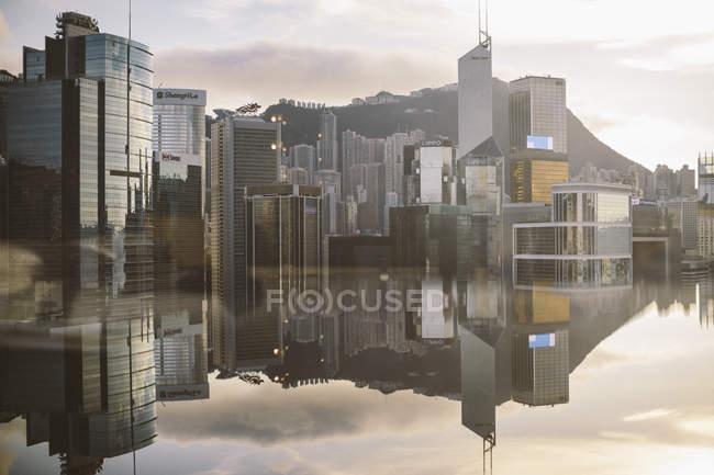 Cityscape з сучасними хмарочосами, відображеними в спокійній морській воді (Гонконг, Китай). — стокове фото