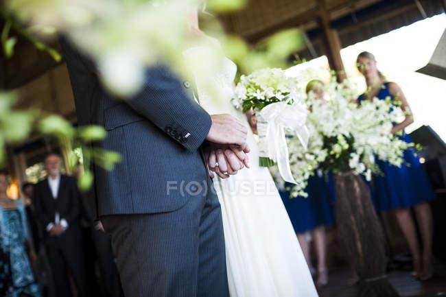 Coupé de mariée et marié tenant la main lors de la cérémonie de mariage . — Photo de stock