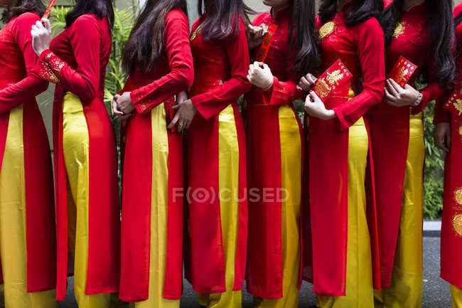Ligne de femmes en robes rouges et jaunes traditionnelles en dehors d'une cérémonie de mariage au Vietnam . — Photo de stock