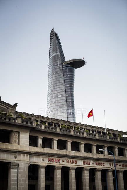 Fassade eines historischen Steingebäudes mit zeitgenössischem Wolkenkratzer in der Ferne, Ho-Chi-Minh-Stadt, Vietnam. — Stockfoto