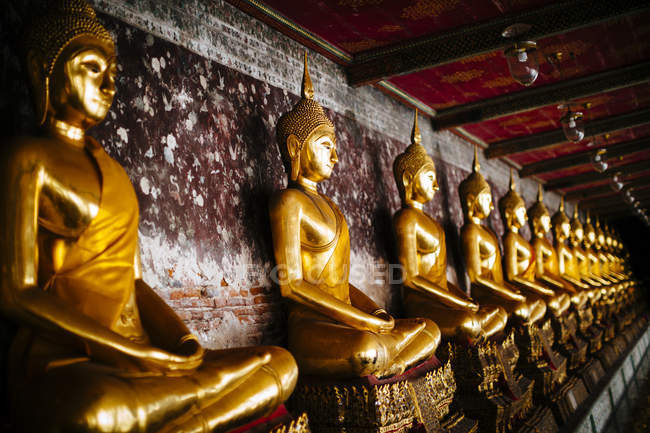 Close-up of a row of golden Buddha statues along a wall, Wat Suthat, Thailand — Stock Photo