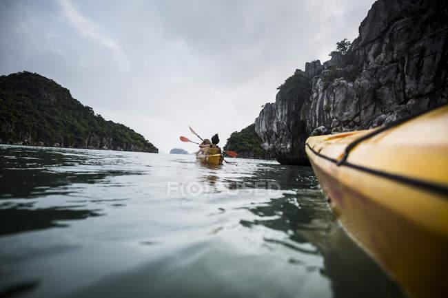 Gruppo di kayaker che remano in una baia tra formazioni carsiche calcaree, Bai Tu Long, Vietnam . — Foto stock
