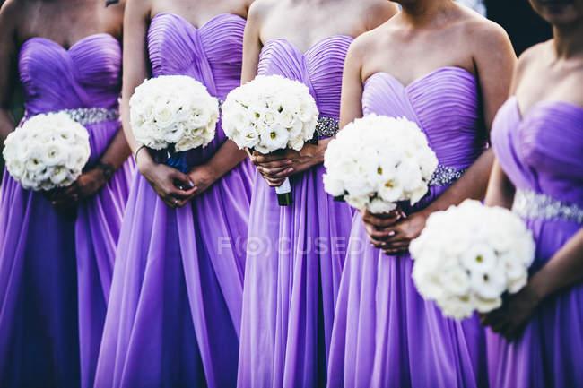 Cérémonie de mariage avec demoiselles d'honneur portant des robes violettes et tenant des fleurs blanches, coupées . — Photo de stock