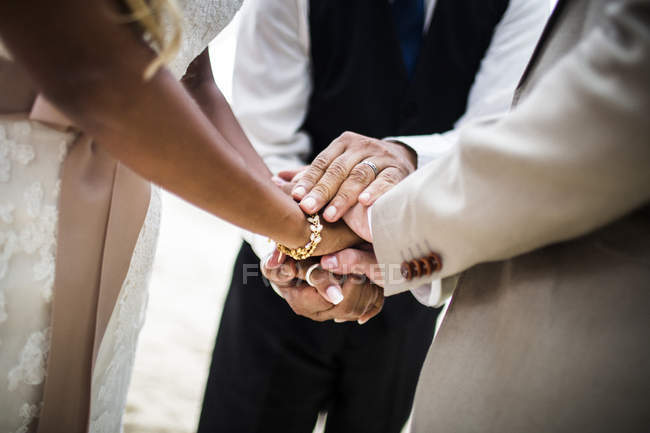 Close-up of a husband and wife joining hands during ceremony at beach. — Stock Photo