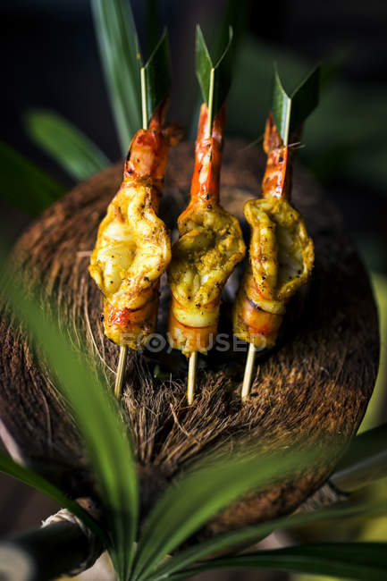 High angle close-up of charcoal-grilled prawn satay on a coconut shell. — Stock Photo