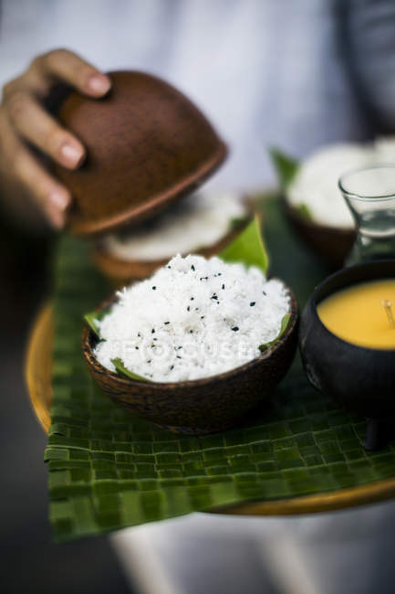 High angle close-up of hand opening bowl of coconut and black sesame seeds body scrub. — Stock Photo