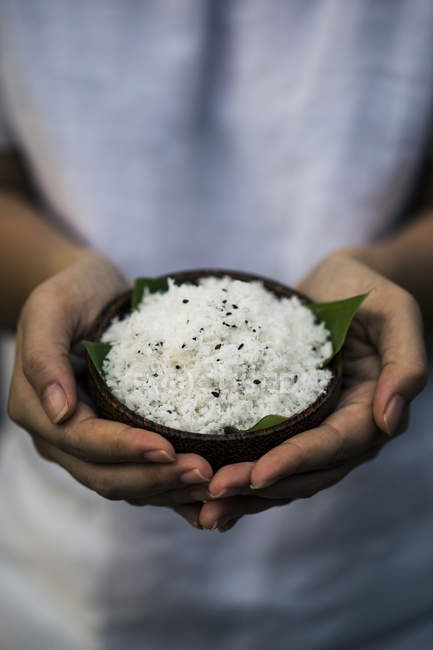 High angle close-up of hands holding bowl of coconut and black sesame seeds body scrub. — Stock Photo