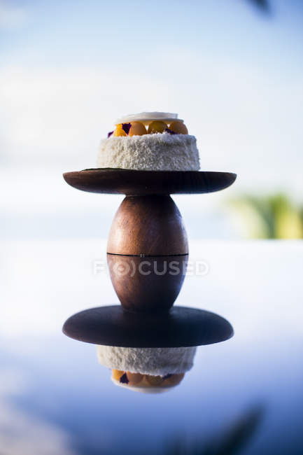 Close-up of coconut and mango cake on cake stand on table with mirror reflection. — Stock Photo