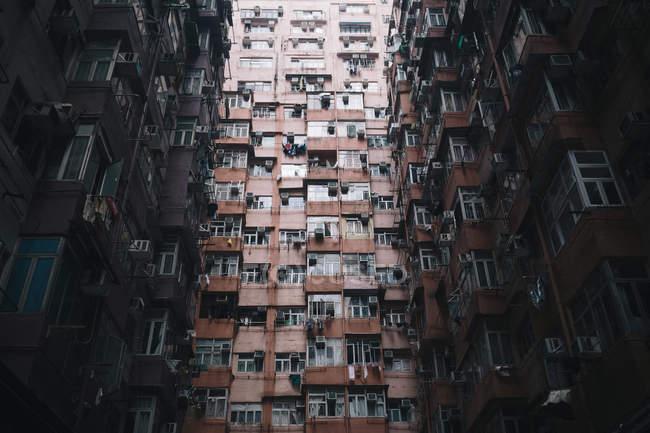 Vista de ángulo bajo de la fachada del imponente complejo residencial con ventanas y balcones, Hong Kong, China - foto de stock